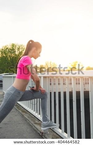 Fit young woman stretching outdoors,on the bridge, healthy lifestyle - stock photo