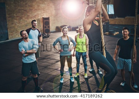 Fit young women climbing a rope in a gym with people on the floor watching - stock photo