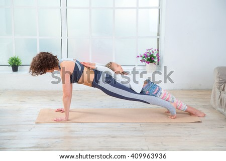 Fitness adult woman with her child. Morning exercises, yoga - do at home all together. Grandmother and granddaughter doing yoga exercise home. Mother and daughter do gymnastics exercises. - stock photo