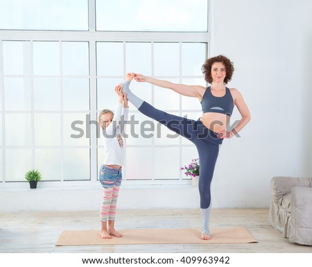 Fitness adult woman with her child. Morning exercises, yoga - do at home all together. Grandmother and granddaughter doing yoga exercise home. Mother and daughter do gymnastics exercises.