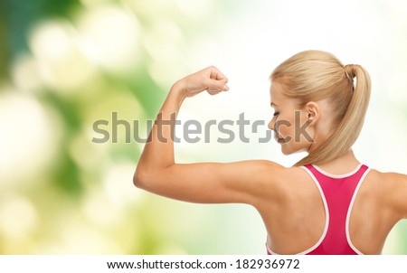 fitness and healtcare concept - young sporty woman showing her biceps - stock photo