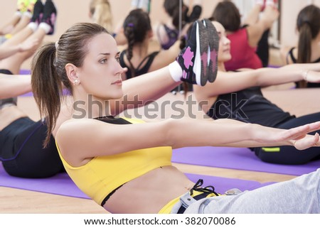 Fitness and Pilates Concepts. Group of  Caucasian Female Athletes Stretching Legs and Arms Muscles on Sport Mats. Horizontal Image - stock photo