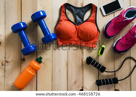 Fitness and sport equipment wooden background on top view
