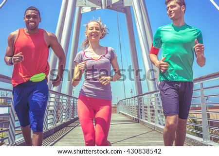 fitness and sports - multi ethnic athletes - 3 people jogging on a bright sunny day with blue sky - healthy lifestyle  concept - stock photo