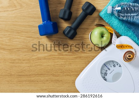 Fitness and weight loss concept, dumbbells, tape measure, white scale towels and water bottle on a wooden table, top view - stock photo