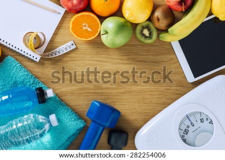 Fitness and weight loss concept, dumbbells, white scale, towels, fruit, tape measure and digital tablet on a wooden table, top view - stock photo
