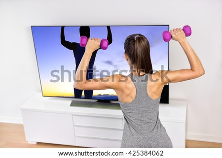 Fitness at home woman working out watching tv. Back of a young sporty girl following workout videos online on smart television, lifting weights toning arms and shoulders exercising strength training.