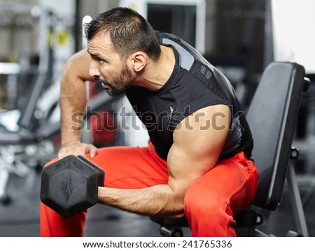Fitness athlete doing biceps workout with dumbbell in a gym - stock photo