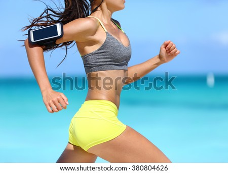 Fitness athlete woman running fast with speed wearing phone armband with touchscreen. Midsection crop showing muscular legs and thighs training glutes during intense cardio workout. - stock photo