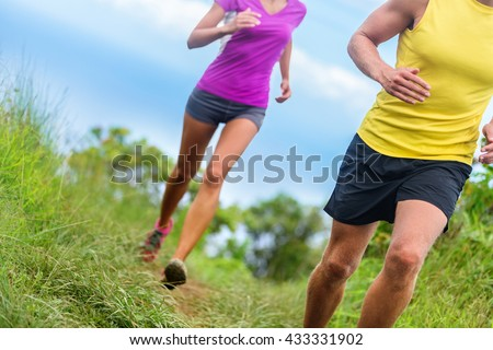 Fitness athletes trail running - athletic legs closeup lower body crop of man and woman working out. Sports people jogging in fast motion marathon race training on a nature path in shorts activewear. - stock photo