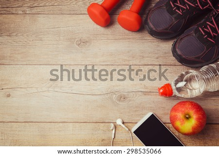 Fitness background with bottle of water, dumbbells and athletic shoes. View from above - stock photo