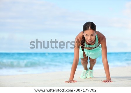 Fitness beach woman smiling planking doing yoga exercises. Happy Asian girl training her abs exercising her core muscles with the plank pose. - stock photo