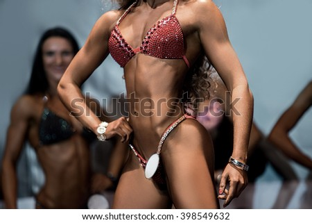 Fitness bikini athlete's slim torso. Female athlete posing on stage. Making the dream come true. Victory is everything. - stock photo