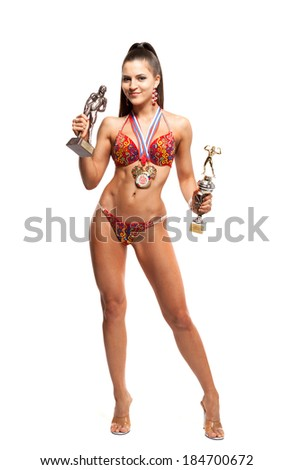 fitness bikini athlete with winning medals isolated on white background - stock photo