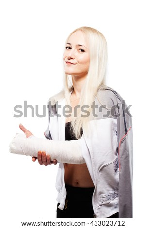 Fitness blond girl with a broken arm in plaster, sports outfit, making thumbs up gesture - stock photo