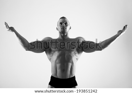 Fitness, bodybuilding. Powerful man on a white background