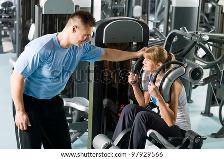 Fitness center young woman exercise with personal trainer on gym machine