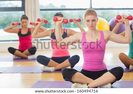 Fitness class and serious trainer lifting dumbbells in the gym - stock photo