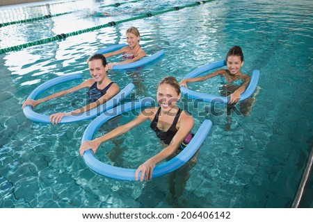 Fitness class doing aqua aerobics with foam rollers in swimming pool at the leisure centre - stock photo