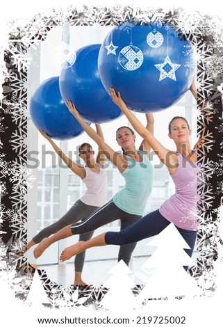 Fitness class doing pilates exercise with fitness balls against christmas themed frame - stock photo