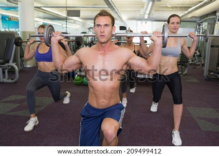 Fitness class lifting barbells together at the gym - stock photo