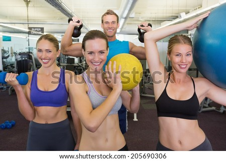 Fitness class posing with different equipment at the gym - stock photo