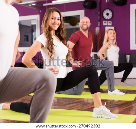 Fitness coach showing to adult learners new exercise at class - stock photo