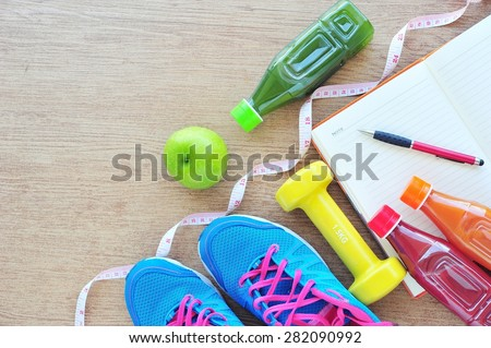 Fitness concept ,fresh fruits, juice bottle and record book on tile floor. - stock photo
