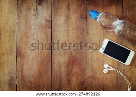 fitness concept with bottle of water, mobile phone with earphones over wooden background. filtered image  - stock photo