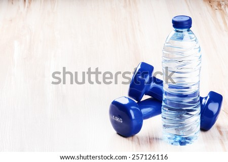 Fitness concept with dumbbells and bottle of water - stock photo