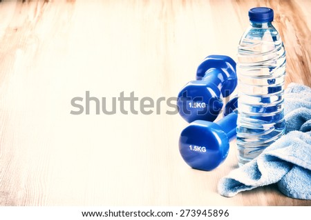Fitness concept with dumbbells and water bottle. After workout setting - stock photo