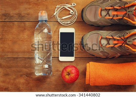 fitness concept with mobile phone , towel, and sport footwear over wooden background.. top view image  - stock photo