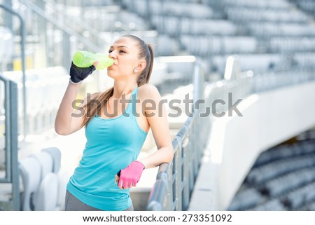 Fitness concept - young woman drinking water during workout, training. Cross fit workout on stairs, squats and exercises - stock photo