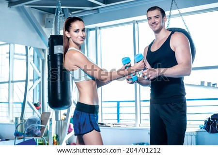 Fitness couple athletes cling dumbbells and looking at the camera and smiling. Young couple athletes men and athletes engaged in training with dumbbells and heavy weights.