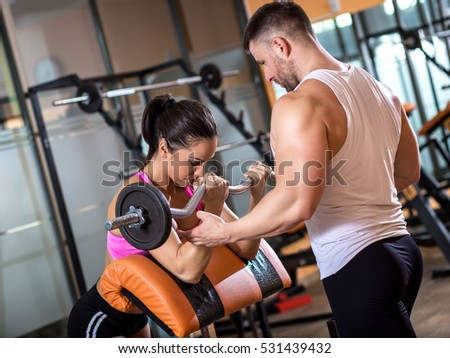 Fitness couple exercising in gym with barbell weights.