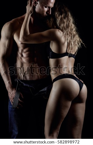 Fitness couple hugging in studio on black background