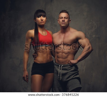 Fitness couple. Massive bodybuilder and athletic brunette woman. - stock photo