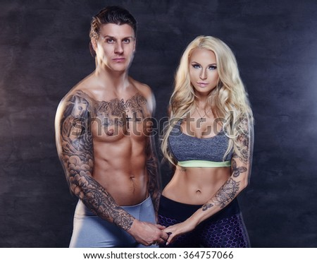 Fitness couple of smiling shirtles tattooed man and sensual blond woman.