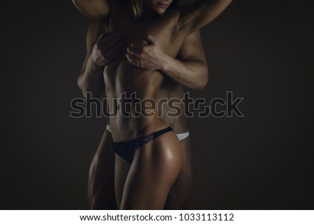 Fitness couple on dark background, shallow depth of field