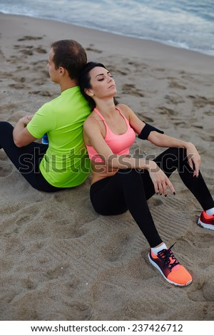 Fitness couple resting after workout sitting on the beach, exhauster after run charming woman taking break leaning on the back of boyfriend, sport couple resting after jogging outdoors sitting on sand - stock photo