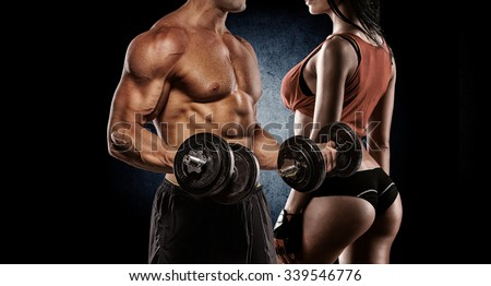Fitness couple - woman and man with dumbbells in gym - stock photo