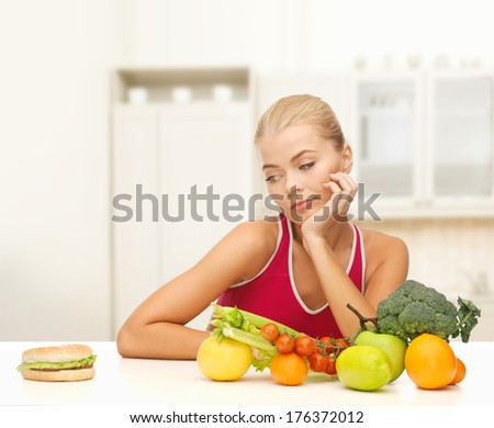fitness, diet and food concept - doubting woman with fruits and hamburger - stock photo