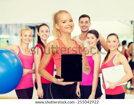 fitness, dieting, technology and sport concept - smiling sporty woman showing tablet pc blank black screen - stock photo