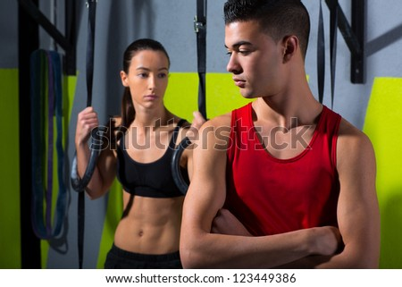 Fitness dip ring man and woman relaxed after workout at gym dipping exercise - stock photo