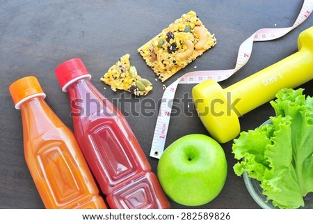Fitness equipment and healthy nutrition on wood background - stock photo