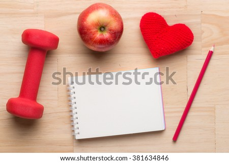Fitness equipment. Healthy food. Apple, dumbbells and measuring tape on wooden background. View from above - stock photo