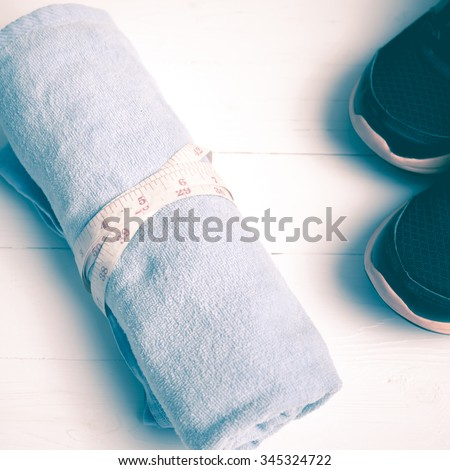 fitness equipment : running shoes,blue towel and measuring tape on white wood table vintage style