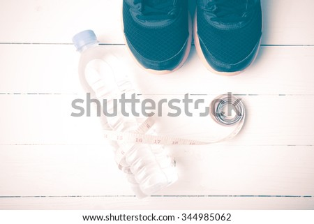 fitness equipment : running shoes,drinking water and measuring tape on white wood table vintage style