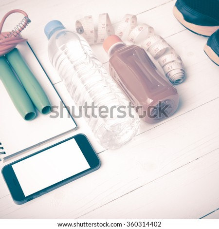 fitness equipment:running shoes,jumping rope,notepad,phone,water,juice and measuring tape on white wood background vintage style