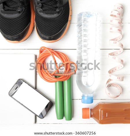 fitness equipment:running shoes,jumping rope,notepad,phone,water,juice and measuring tape on white wood background